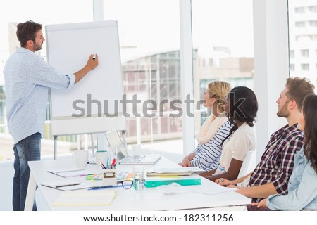 Man presenting an idea to his co workers in creative office - stock photo