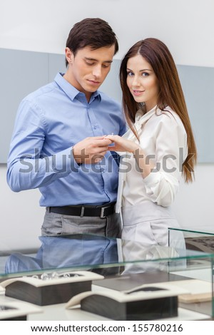 Man presents engagement ring to his woman at jeweler's shop. Concept of wealth and luxurious life - stock photo