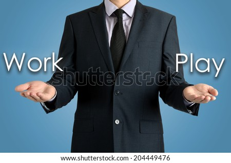 man presents with their hands for a decision problem between work or play on blue background - stock photo