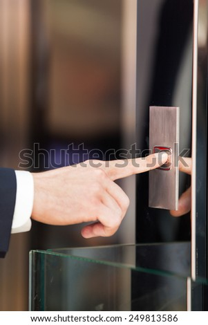 Man pressing red elevator button. closeup on businessman finger pushing elevator button  - stock photo