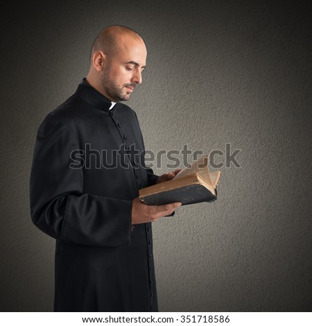 Man priest reads the bible sacred text - stock photo