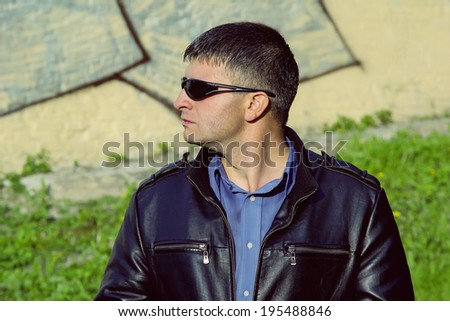 Man private security at work. Security guard in dark glasses watching the situation around. Serious man in a black jacket. Toned photograph in dark colors to give serious work private security. - stock photo