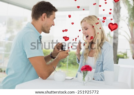 Man proposing marriage to his shocked blonde girlfriend against red heart balloons floating - stock photo