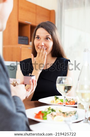 Man proposing to his girlfriend while they are having romantic dinner - stock photo