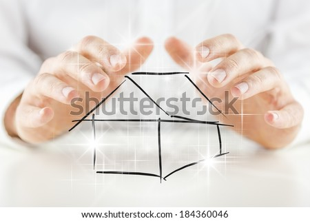 Man protecting a hand-drawn black and white sketch of a house with his hands with a multiple bright shining star effect in a conceptual image. - stock photo