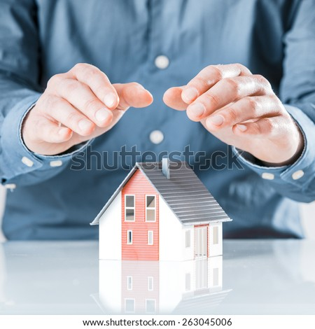 Man protecting his house with cupped hands conceptual of insurance, risk, security, investment, protection and ownership - stock photo