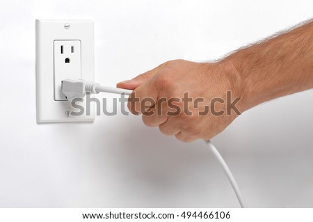 Man Pulling Electrical Plug from Wall Socket on White