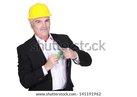 Man pulling money out of his pocket - stock photo