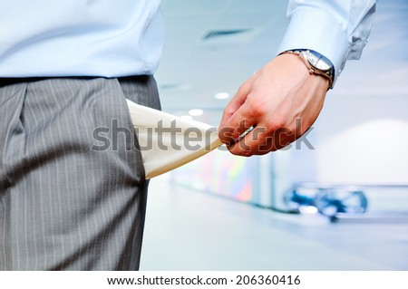 Man Pulling out Empty Pocket  on office background - stock photo