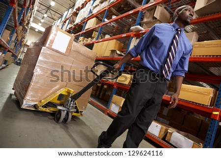 Man Pulling Pallet In Warehouse - stock photo