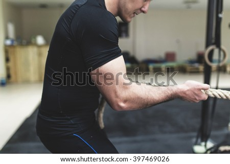 Man pulling rope during workout. Depth of field, selective focus, motion blur - stock photo