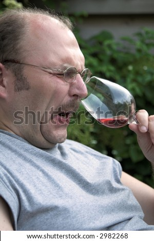 Man pulling up his nose in disgust while smelling a glass of wine - stock photo