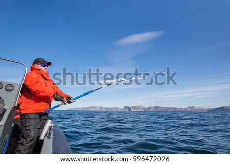 man pulls a fish out of water. Red Jacket. sports glasses. fisherman