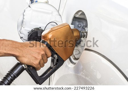 man pumping gasoline fuel in car at gas station - stock photo