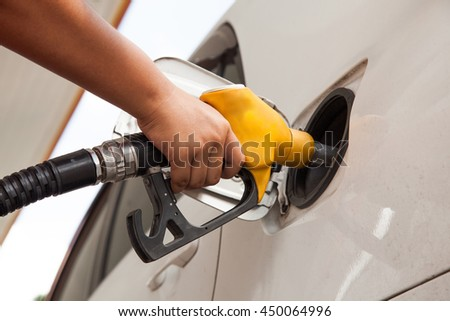 Man pumping gasoline fuel in car at gas station.
