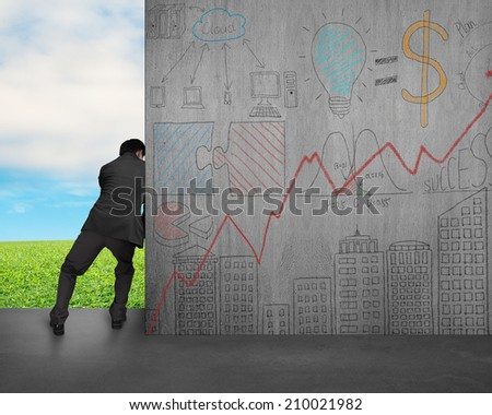 man push away concrete wall with doodles on sky and grass background