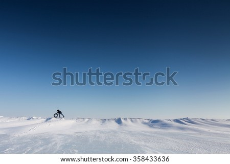 Man pushes a wheel on a snowy surface - stock photo
