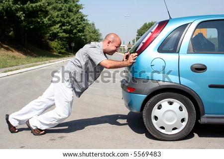 Man pushing a broken car or a car out of gas - stock photo