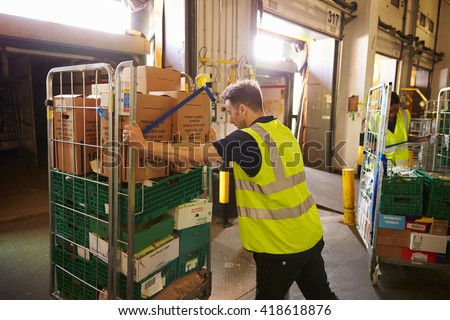 Man pushing a roll cage ready for delivery in a warehouse - stock photo