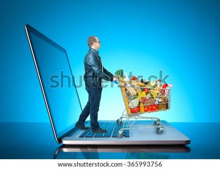 man pushing a shopping cart on laptop - stock photo