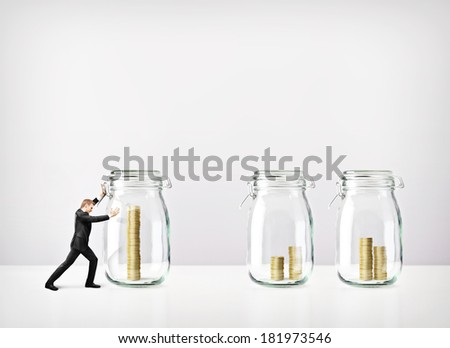 Man pushing glass jars with coins - stock photo
