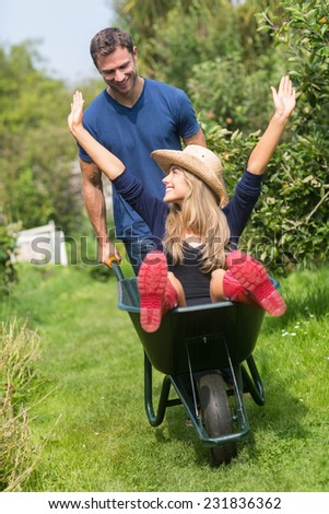 Man pushing his girlfriend in a wheelbarrow at home in the garden - stock photo