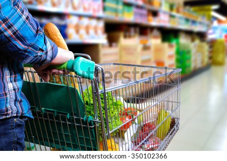 Man pushing shopping cart full of food in the supermarket aisle. Elevated rear view. horizontal composition - stock photo