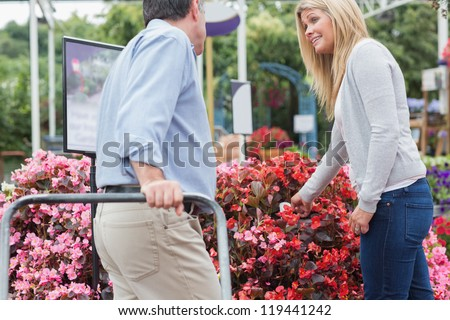 Man pushing the trolley while talking with woman - stock photo
