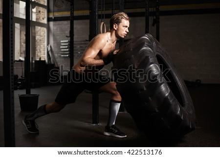 Man pushing tire in gym - stock photo