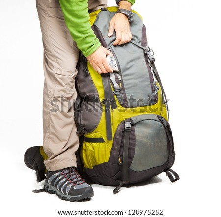 Man put camera into the pocket of packed backpack - stock photo
