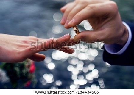 Man puts his finger on the bride wedding ring - stock photo