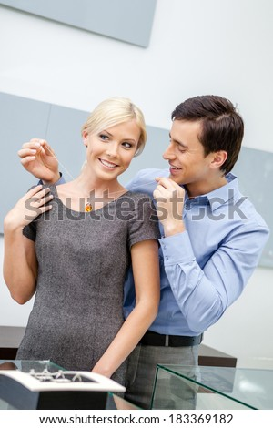 Man puts necklace on his girlfriend at jeweler's shop. Concept of wealth and luxurious life - stock photo