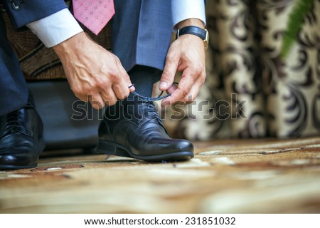 Man puts on shoes. Focus on the laces - stock photo