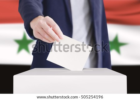 Man putting a ballot into a voting box with Syrian flag on background.