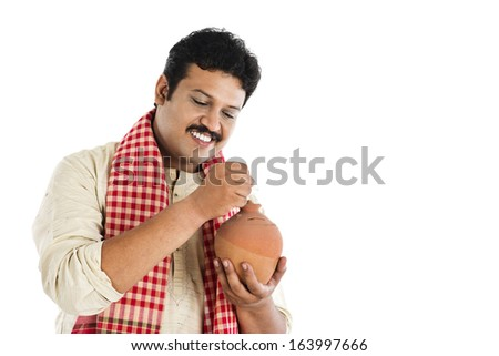 Man putting a coin into a piggy bank and smiling - stock photo
