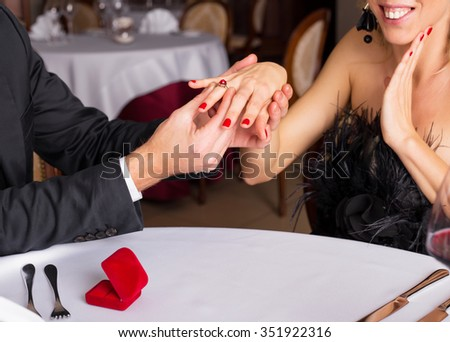 Man putting an engagement ring on woman's finger  - stock photo