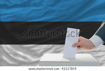 man putting ballot in a box during elections in estonia in front of flag