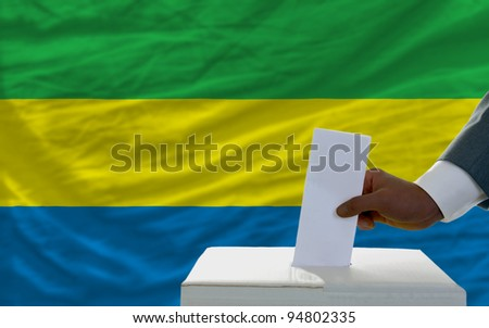 man putting ballot in a box during elections  in front of national flag of gabon - stock photo