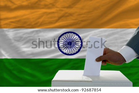 man putting ballot in a box during elections  in front of national flag of india - stock photo