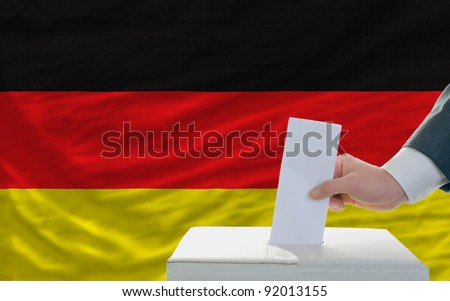 man putting ballot in a box during elections in germany - stock photo