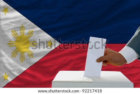 man putting ballot in a box during elections in philippines in front of flag - stock photo