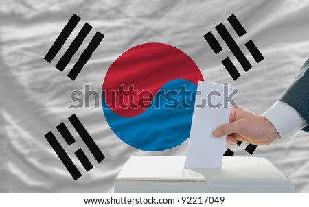 man putting ballot in a box during elections in south korea in front of flag - stock photo