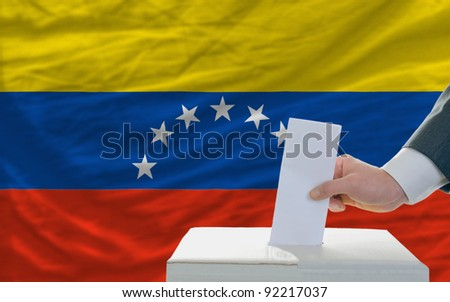 man putting ballot in a box during elections in venezuela in front of flag - stock photo