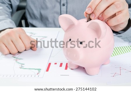 Man putting coin in piggy bank. Saving money concept