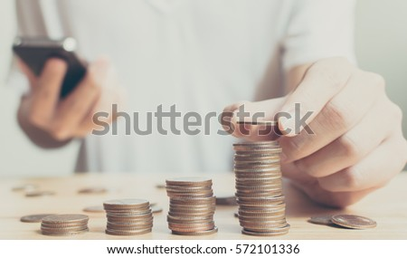 Man putting coins on stack with holding smartphone, Concept business, finance, money saving