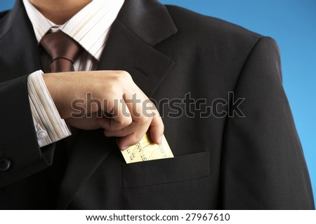 man putting credit card to the pocket - stock photo