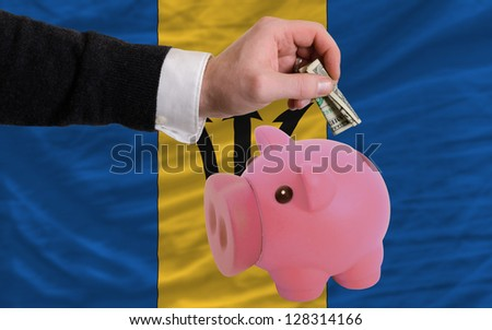 Man putting dollar into piggy rich bank national flag of barbados in foreign currency because of inflation - stock photo