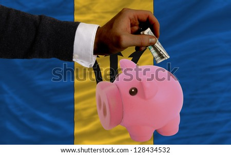 Man putting dollar into piggy rich bank national flag of barbados in foreign currency because of inflation