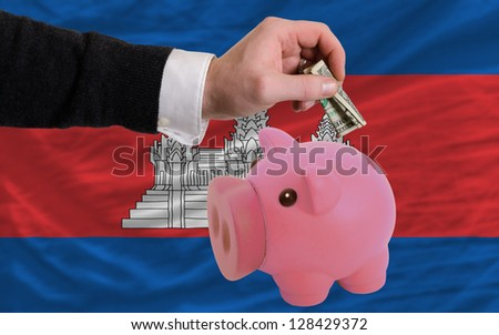 Man putting dollar into piggy rich bank national flag of cambodia in foreign currency because of inflation - stock photo