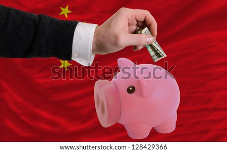 Man putting dollar into piggy rich bank national flag of china in foreign currency because of inflation - stock photo